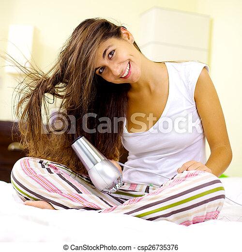 Happy woman blow drying long hair at home - csp26735376