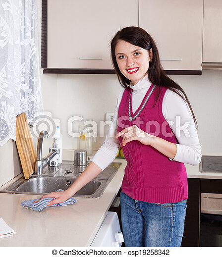 Happy woman cleaning  kitchen at home - csp19258342