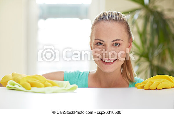 happy woman cleaning table at home kitchen - csp26310588