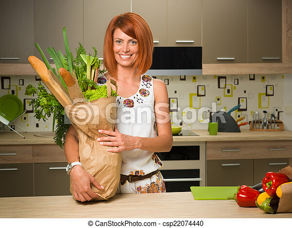 happy woman holding bag with groceries - csp22074440