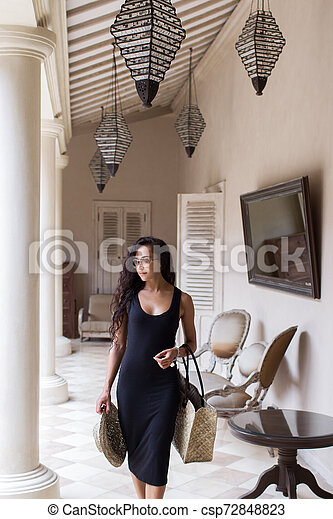Happy woman in black dress with straw bag in mall with white walls and columns - csp72848823