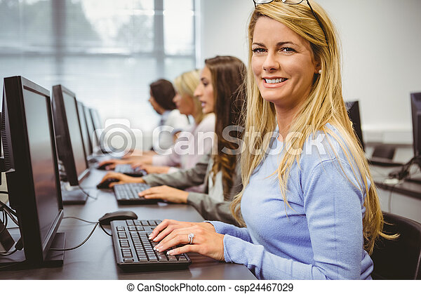 Happy woman in computer room smiling at camera - csp24467029
