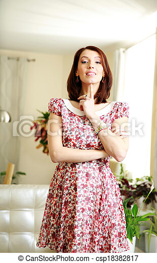 Happy woman in dress standing at home - csp18382817