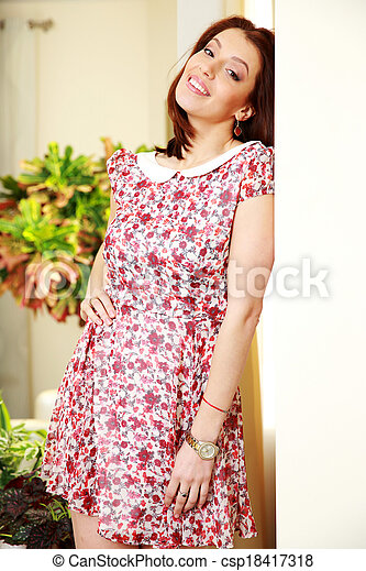 Happy woman in dress standing at home - csp18417318
