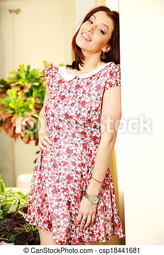 Happy woman in dress standing at home - csp18441681