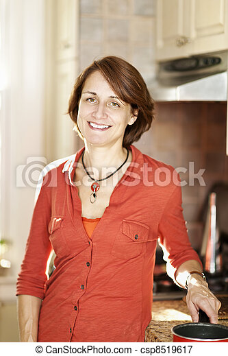 Happy woman in kitchen at home - csp8519617
