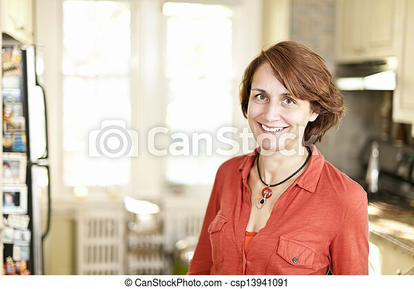Happy woman in kitchen at home - csp13941091