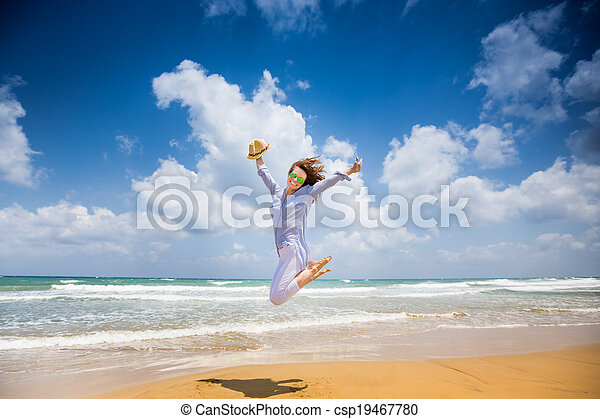 Happy woman jumping at the beach - csp19467780