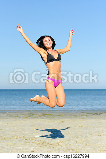 Happy woman jumping at the beach - csp16227994