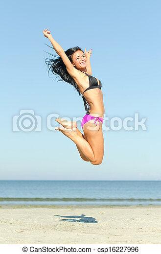 Happy woman jumping at the beach - csp16227996
