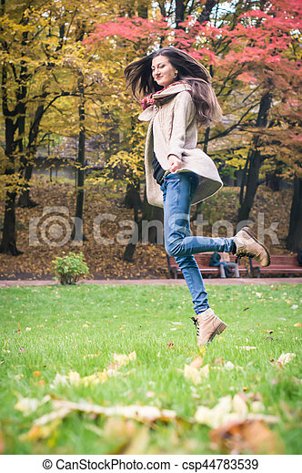 happy woman jumping on grass - csp44783539