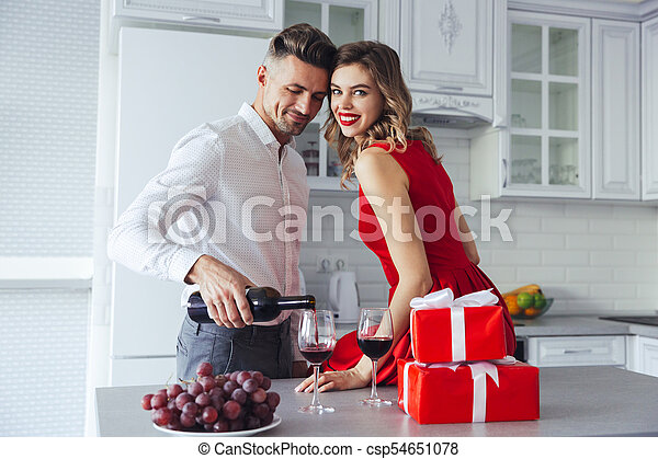 Happy woman looking camera while her man pouring wine into glasses at home - csp54651078