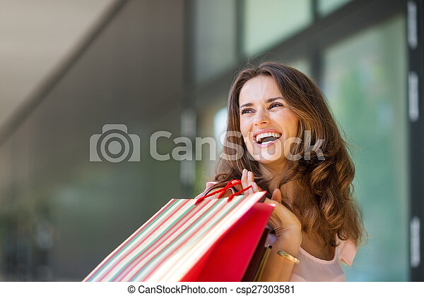 Happy woman out shopping, holding up colourful shopping bags - csp27303581