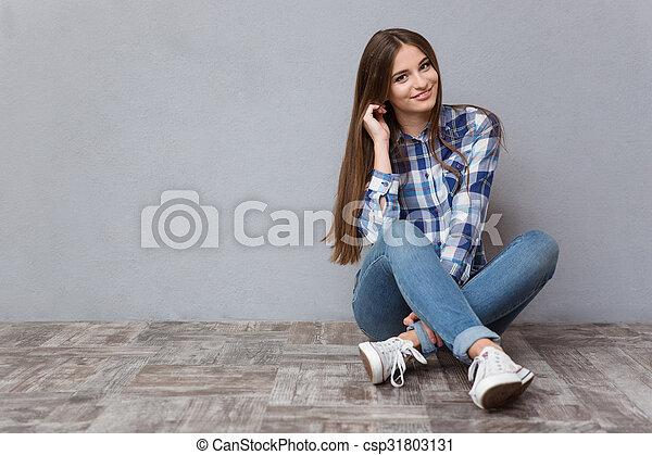 Happy woman sitting on the floor - csp31803131