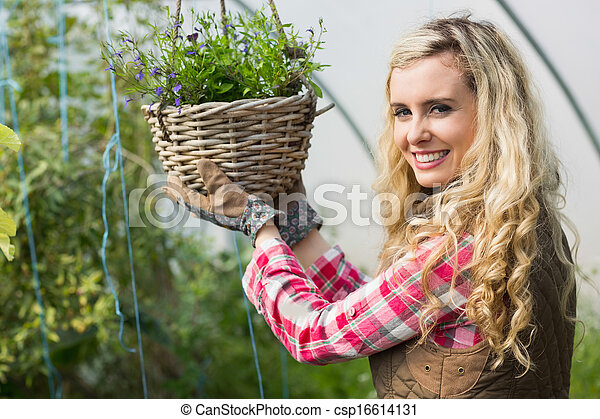 Happy woman touching a hanging flower basket - csp16614131
