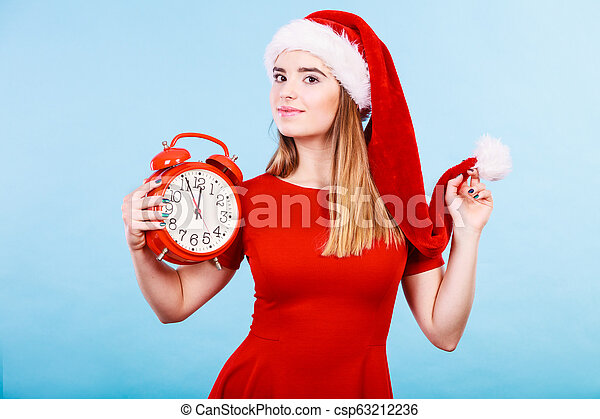 Happy woman wearing Santa Claus costume holding clock - csp63212236