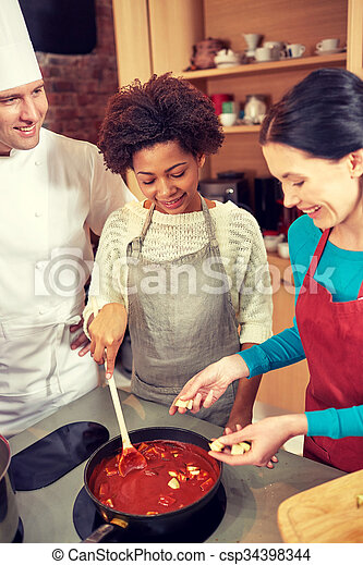 happy women and chef cook cooking in kitchen - csp34398344