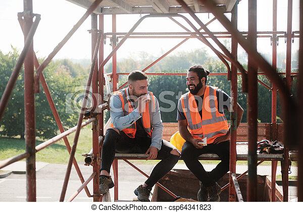 Happy Workers In Construction Site During Lunch Break - csp64341823
