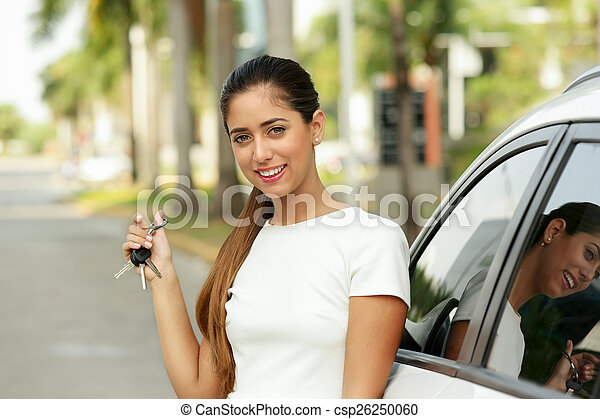 Happy young adult smiling and showing keys of new car - csp26250060