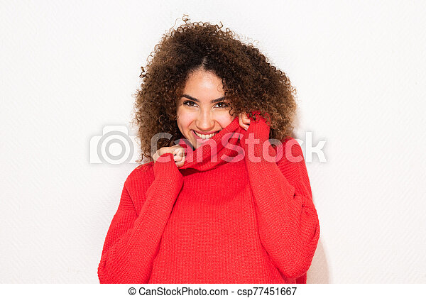 happy young african american woman holding sweater - csp77451667