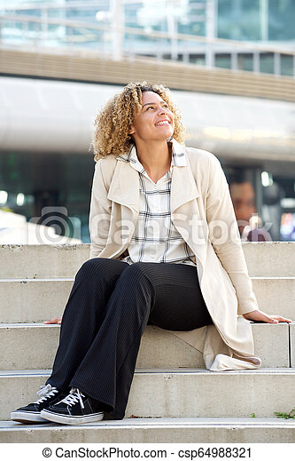 happy young african american woman sitting on steps in city - csp64988321