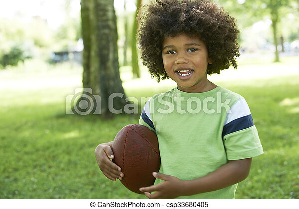 Happy Young Boy Playing In Park With American Football - csp33680405