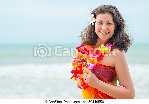 Happy young brunette in pareo and flower lei against the sea - csp50449556