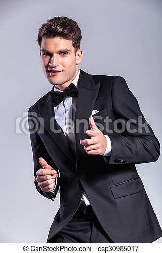 Happy young business man pointing at the camera - csp30985017