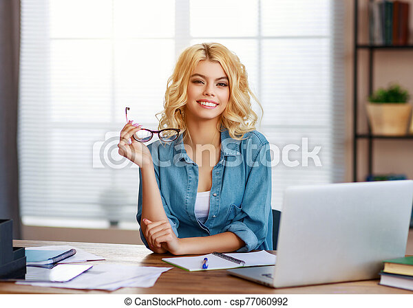 happy young business woman at home office working on computer - csp77060992