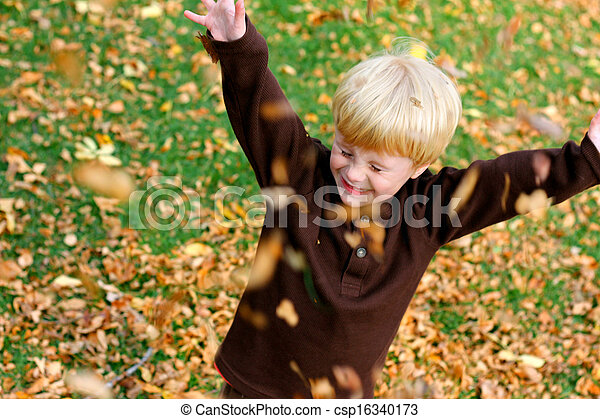 Happy Young Child Playing Outside in The Fallen Leaves - csp16340173