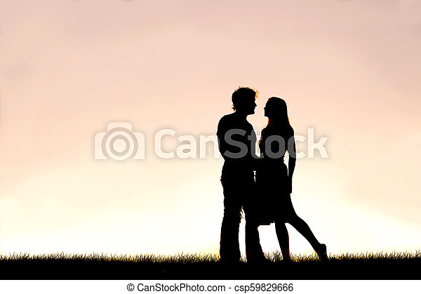Happy Young Couple in Love Silhouetted Against Sunset in the Sky - csp59829666