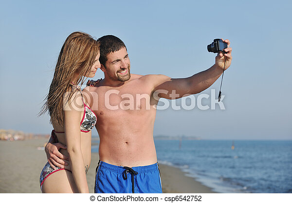 happy young couple in love taking photos on beach - csp6542752