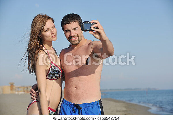 happy young couple in love taking photos on beach - csp6542754