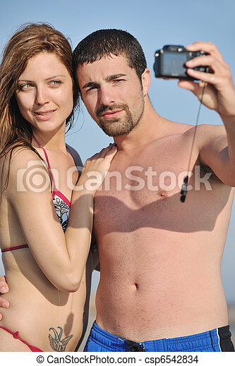 happy young couple in love taking photos on beach - csp6542834