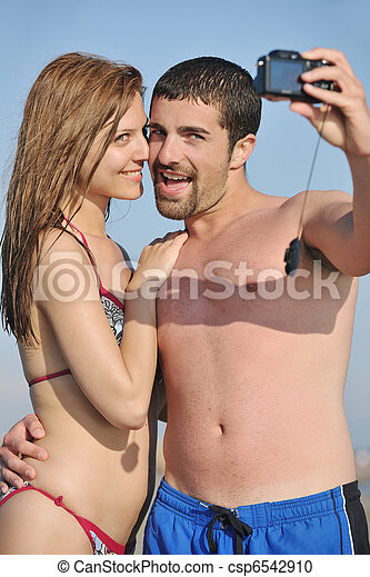 happy young couple in love taking photos on beach - csp6542910