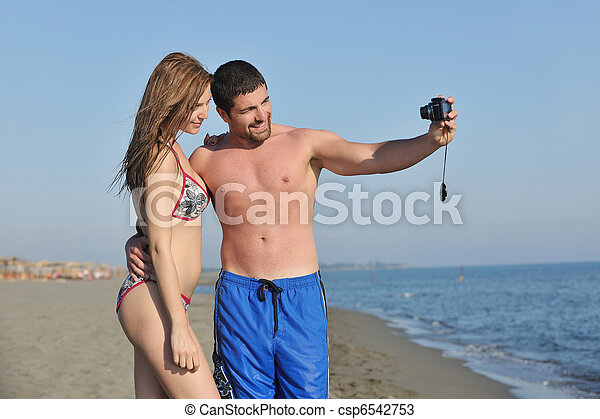 happy young couple in love taking photos on beach - csp6542753