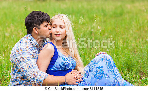 Happy young couple relaxing on the lawn in a summer park. Love concept. Vacation. - csp48111545
