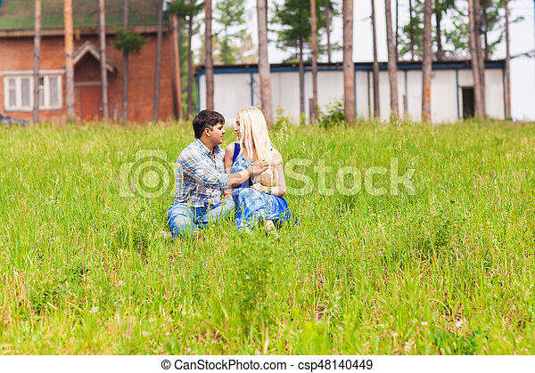 Happy young couple relaxing on the lawn in a summer park. Love concept. Vacation. - csp48140449