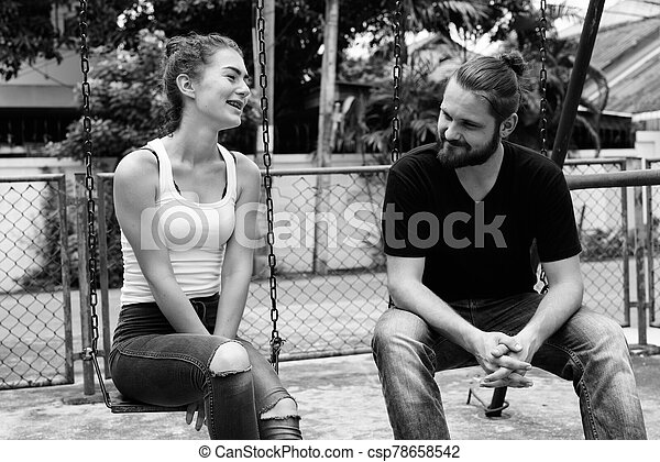 Happy young couple smiling and sitting on the metal swings together in the old playground - csp78658542