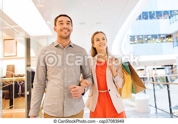 b291b33366 Happy young couple with shopping bags in mall. Sale, consumerism and ...