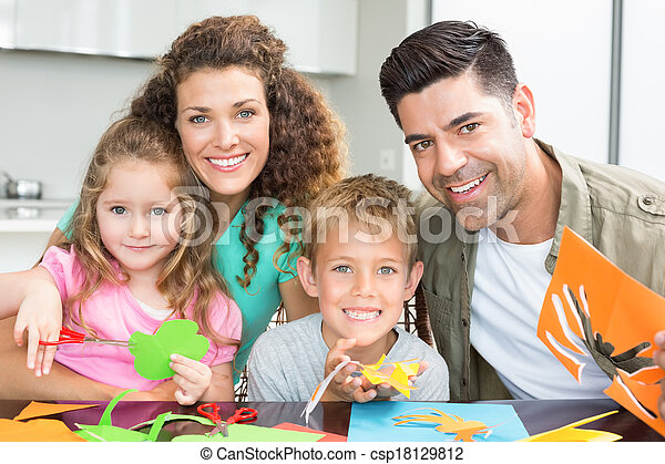 Happy young family doing arts and crafts at the table - csp18129812