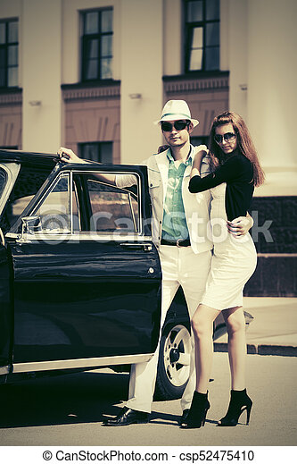 Happy young fashion couple in love next to vintage car - csp52475410