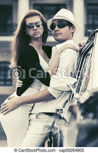 Happy young fashion couple in love next to vintage car - csp56264905