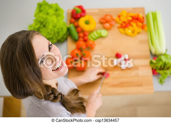 Happy young housewife cutting fresh vegetables - csp13634457