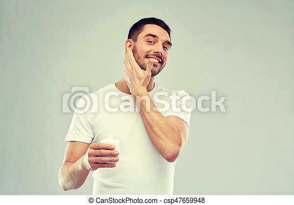 happy young man applying cream or lotion to face - csp47659948