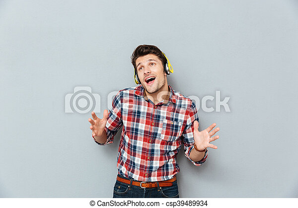 Happy Young Man In Headphones Listening To Music And Singing