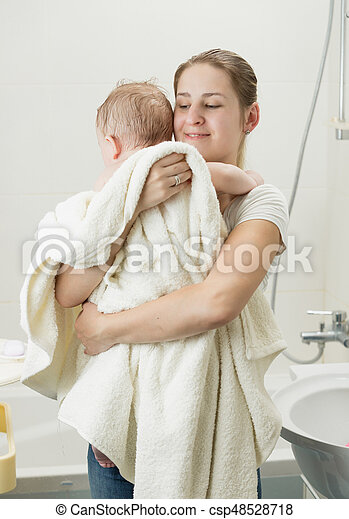 Happy young mother holding her baby after having bath - csp48528718