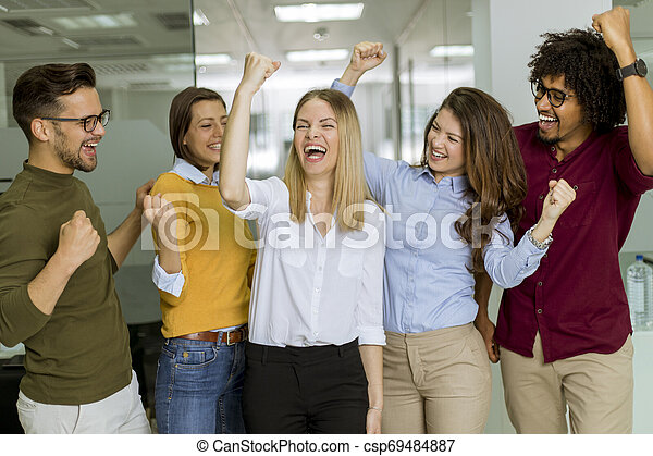 Happy young people are standing in a modern office - csp69484887