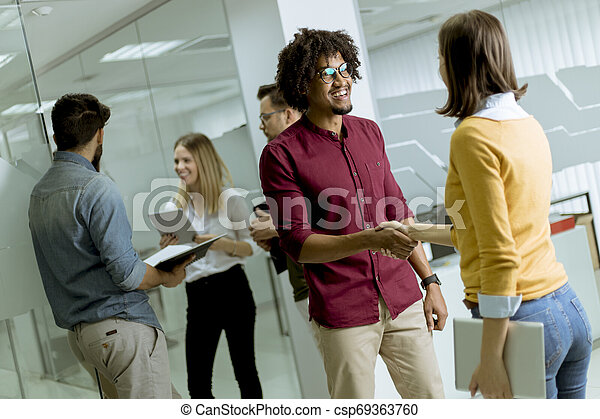Happy young people are standing in a modern office - csp69363760
