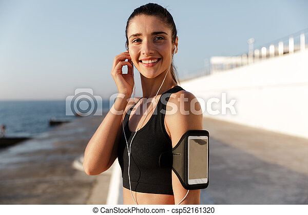 Happy young sports woman listening music outdoors. - csp52161320